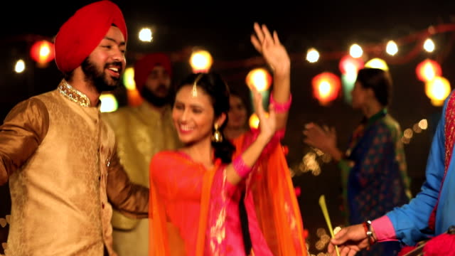 punjabi couple dancing in lohri festival, punjab, india - punjab india stock videos and b-roll footage
