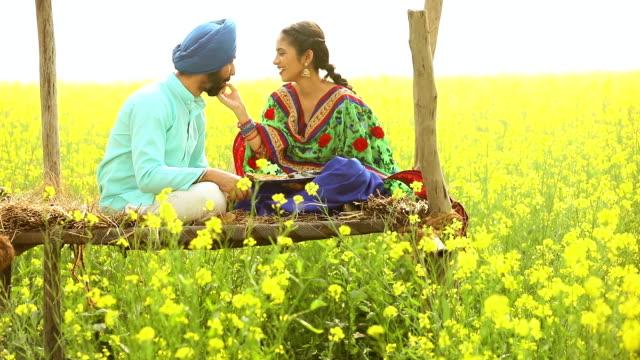 punjabi couple eating food in the mustard farm, punjab, india - turban stock videos & royalty-free footage