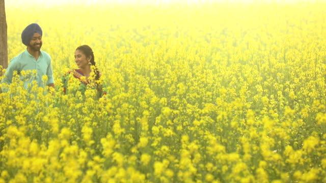 Punjabi couple running in the mustard farm, Punjab, India