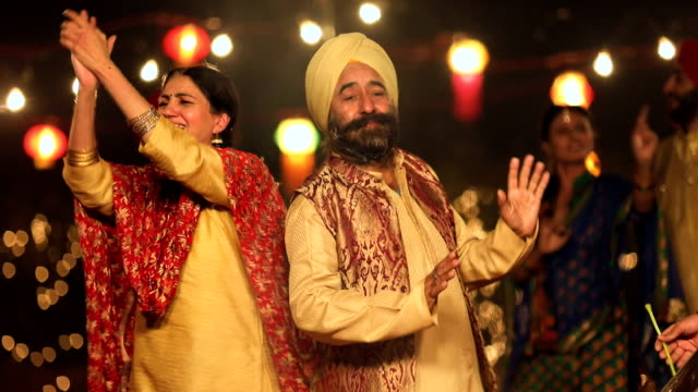 punjabi senior couple dancing in lohri festival, punjab, india - punjab india stock videos and b-roll footage