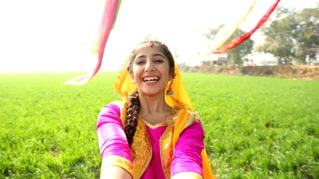 Punjabi young woman playing kikli dance in the farm, Punjab, India