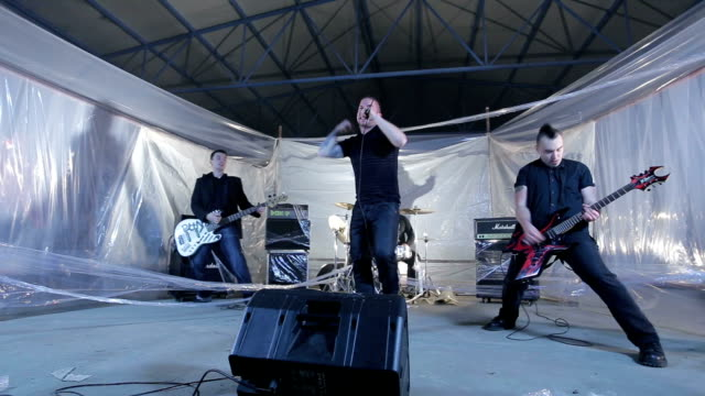 vídeos de stock e filmes b-roll de punk band performing in abandoned warehouse - música heavy metal