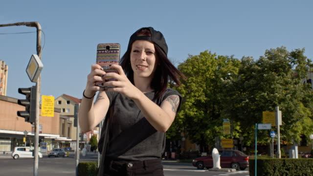 vídeos de stock e filmes b-roll de slo mo punk menina com uma chamada de vídeo na cidade - música heavy metal