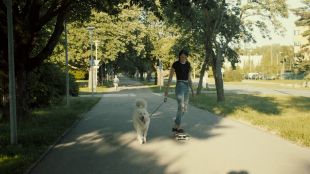punk girl skateboarding with the pet dog (slow motion) - punk person stock videos & royalty-free footage