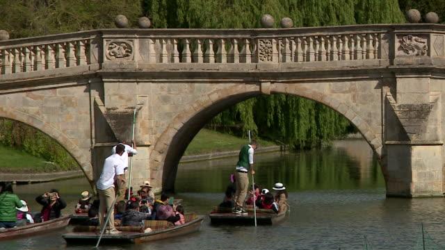 vídeos de stock, filmes e b-roll de punting in cambridge down the river cam past king's college and mathematical bridge - king's college cambridge
