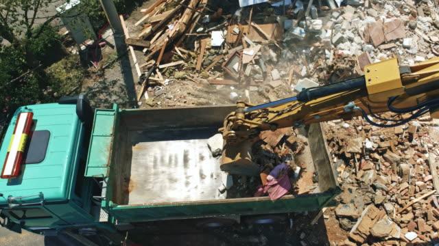 vidéos et rushes de aerial remorque pup chargé de débris sur le site de la démolition d'un immeuble ancien - semi remorque