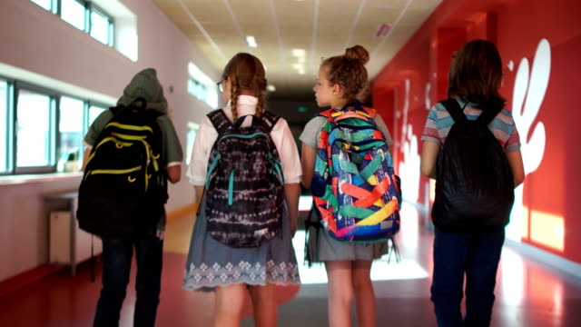 Pupils go through the school corridor. Two boys and two girls. Children carry backpacks. Back to school. Back view