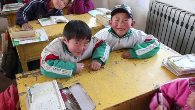 vidéos et rushes de ms pupils in a rural classroom/baoji,shaanxi,china - casquette