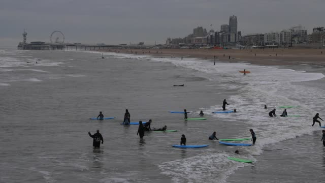 pupils surf during class in the water of the north sea on the beach of scheveningenon october 19, 2020 in the hague, the netherlands. for a few days... - silver coloured stock videos & royalty-free footage