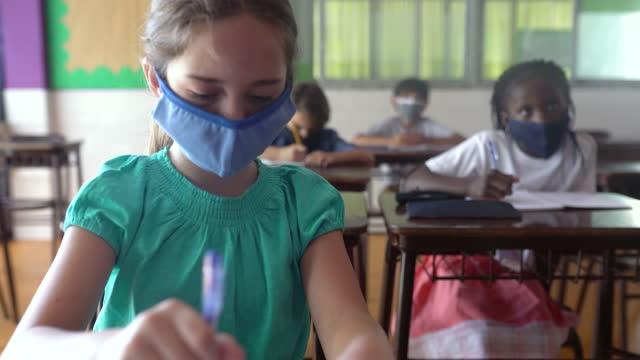 生徒たちはフェイスマスクを着用し、教室で授業を行っています。コーヴィッド-19 コンセプト - 消しゴム点の映像素材/bロール