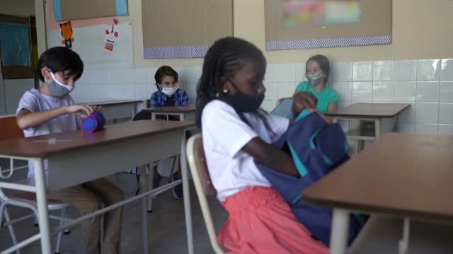 生徒たちはフェイスマスクを着用し、教室でバックパックから学校の教材を取り出します。コーヴィッド-19 コンセプト - 消しゴム点の映像素材/bロール