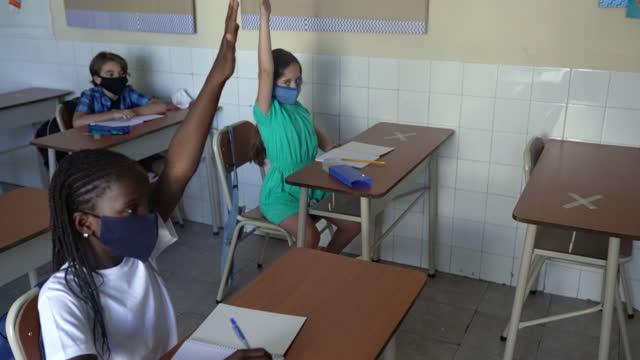 フェイスマスクを着用し、教室で手を挙げる生徒たち。covid-19 コンセプト。 - 消しゴム点の映像素材/bロール