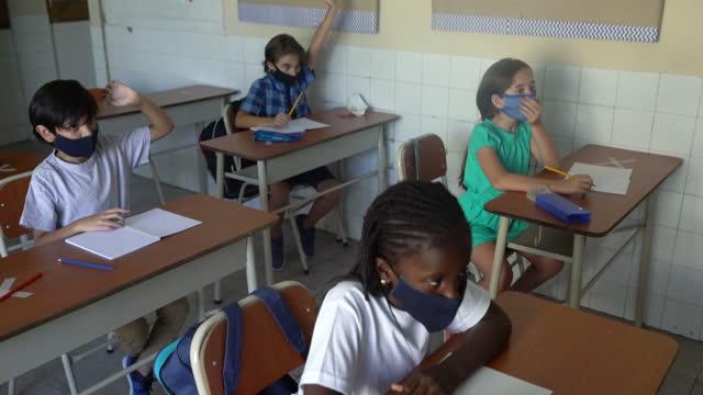 フェイスマスクを着用し、教室で手を挙げる生徒たち。コーヴィッド-19 コンセプト - 消しゴム点の映像素材/bロール
