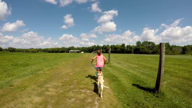 vidéos et rushes de puppy and girl running away from camera - children only