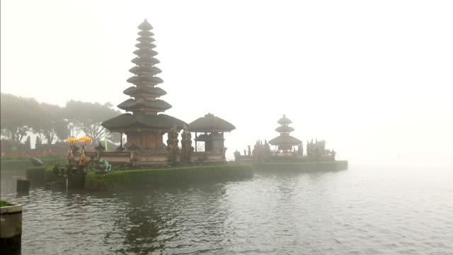 vidéos et rushes de pura ulun danu bratan est un temple majeur de l'eau sur le lac bratan dans la brume après la pluie, bali, indonésie - spiritualité