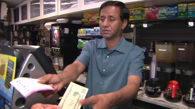 stockvideo's en b-roll-footage met purchasing a lottery ticket on august 01, 2013 in new york, new york - loterijlootje