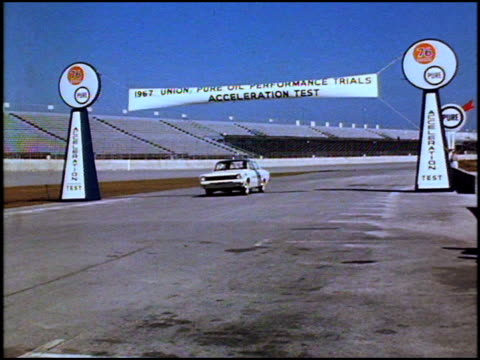 ws pure oil flag flying / ws daytona speedway timing and press booth / ws acceleration test banner rambler drives under it toward camera / same as... - circuito di daytona video stock e b–roll