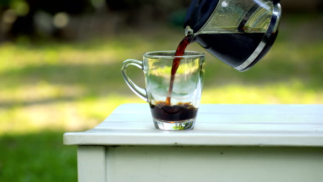 puring coffee from pot to clear glass, in garden - transparent stock videos & royalty-free footage