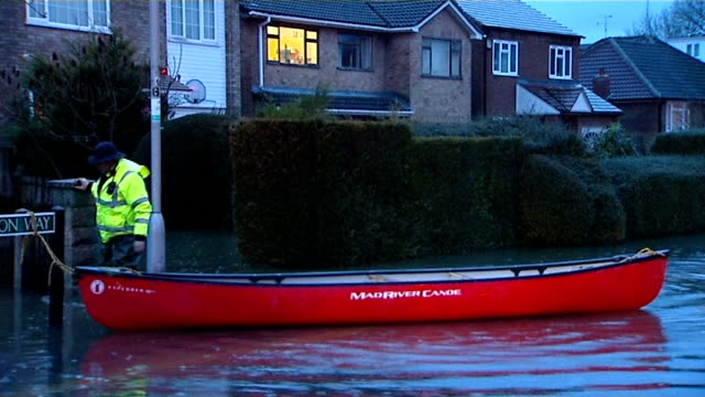 Berkshire Purley on Thames EXT Local resident pulling canoes and wading through flooded road / Canoes tied to street sign and floating in water / Man...