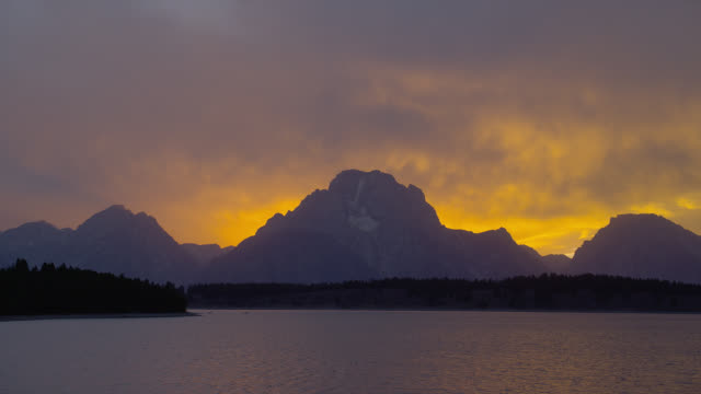a purple and gold sky glows above jackson lake and mount moran in grand teton national park. - mt moran stock videos & royalty-free footage