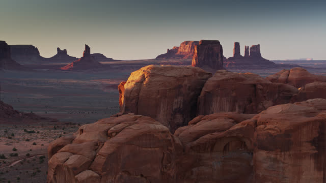 purple and orange evening light on mitten buttes in monument valley - butte rocky outcrop stock videos and b-roll footage