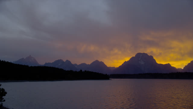 a purple and orange sky glows above mount moran and jackson lake in grand teton national park. - mt moran stock videos & royalty-free footage