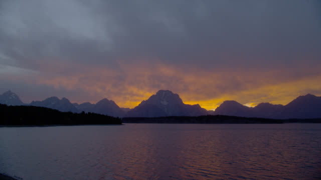 stockvideo's en b-roll-footage met a purple and orange sky glows above the grand tetons and jackson lake in grand teton national park. - mount moran