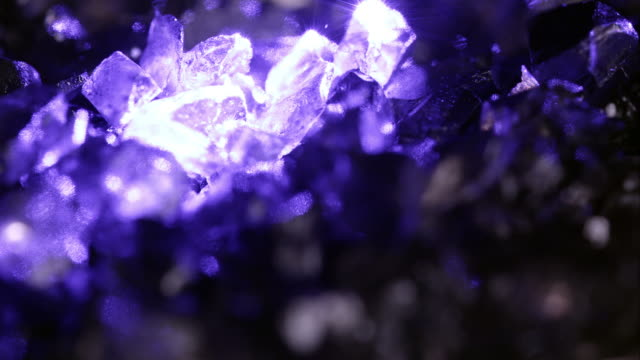 Purple glow shining off small rocks spinning