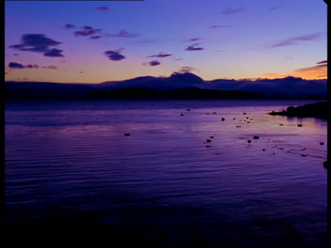 a purple golden hour sky reflects in a calm lake. - golden hour stock videos & royalty-free footage
