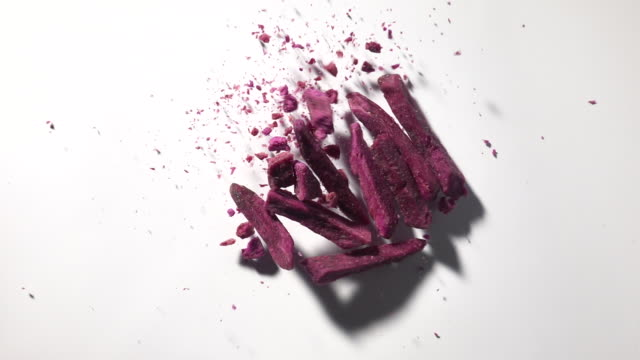 vidéos et rushes de purple potato yam dehydrated food in mid air captured with high speed with white background - igname