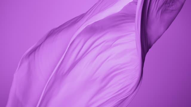 Purple silky Fabric Flowing By Wind in purple background, Slow Motion