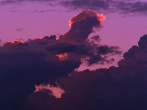 Purple sky with silhouetted clouds rolling