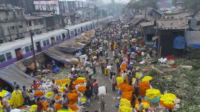 A purple train speeds by the flower market in Calcutta.