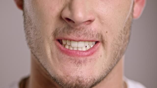 stockvideo's en b-roll-footage met samengeknepen lippen van een jonge en boze blanke man - tanden op elkaar klemmen
