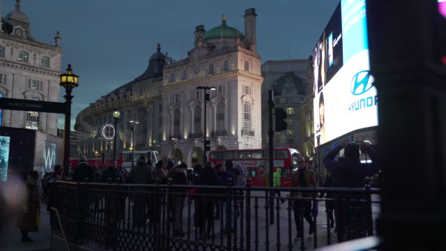 push in as traffic and pedestrians pass in front of the bright lights of piccadilly circus, london - video wall stock videos & royalty-free footage