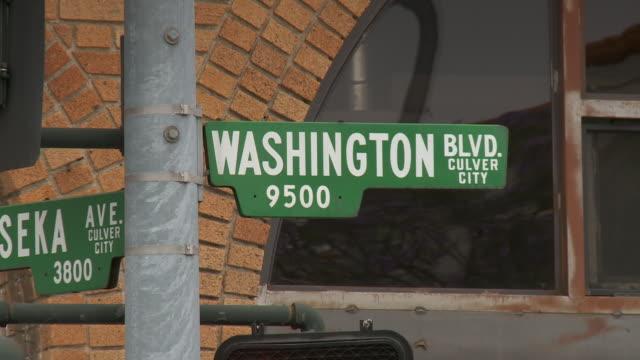 vídeos de stock, filmes e b-roll de push in of the washington blvd street sign in culver city los angeles, hollywood studios - hollywood califórnia