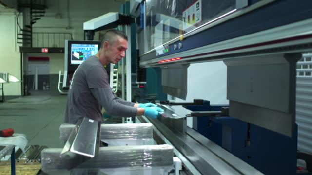 push in on medium profile shot of man bending a piece of metal in a machine. - einzelner mann über 30 stock-videos und b-roll-filmmaterial