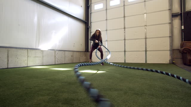 push in pull out, young woman lifting heavy ropes in a gym - pull out camera movement stock videos & royalty-free footage