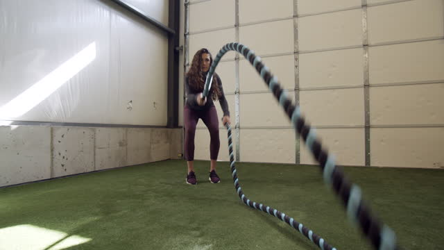 push in, pull out, young woman working out with heavy ropes in a gym - pull out camera movement stock videos & royalty-free footage