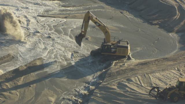 push in shot of an excavator at work to the manasquan beach erosion project - eroded stock videos & royalty-free footage