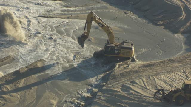 stockvideo's en b-roll-footage met push in shot of an excavator at work to the manasquan beach erosion project - geërodeerd