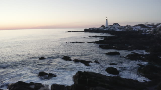 vidéos et rushes de push in shot of the portland head light at sunset - maine
