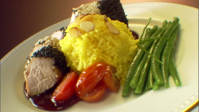 Push in to a close-up of a rotating dinner plate of sliced pork and yellow rice.