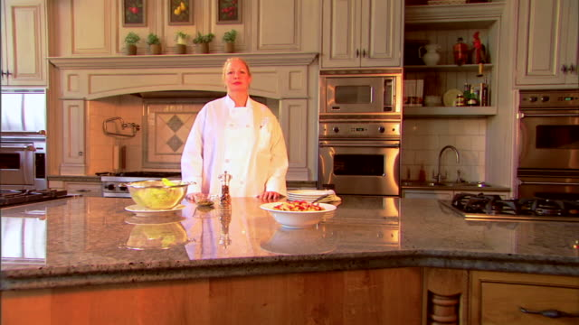 push in to a portrait of a chef in the kitchen shrugging her shoulders while looking at the viewer. - push in stock videos & royalty-free footage