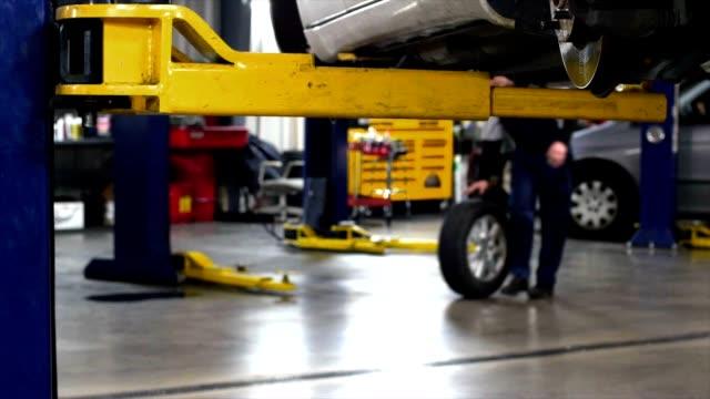 vidéos et rushes de push rolling car tire in the repair shop - partie de véhicule