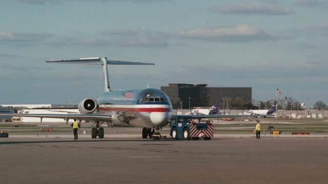 a pushback tractor guides an american airlines passenger jet backwards on a tarmac. - エプロン点の映像素材/bロール