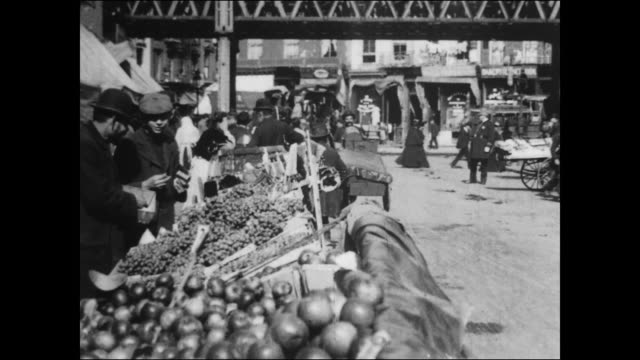pushcart vendors sell their goods fruit and vegetable carts / elevated railroad track crosses over the street in the background / policeman scolds... - lower east side bildbanksvideor och videomaterial från bakom kulisserna