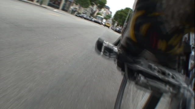 pov push-in - a leg pedals a bicycle over a street and around a corner. / san francisco, california, usa - moving past stock videos & royalty-free footage