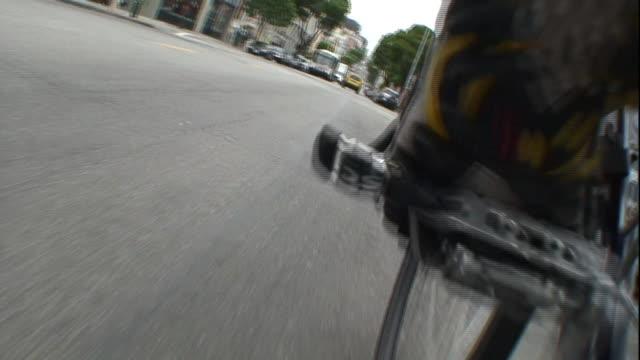 pov push-in - a leg pedals a bicycle over a street and around a corner. / san francisco, california, usa - gå vidare aktivitet bildbanksvideor och videomaterial från bakom kulisserna