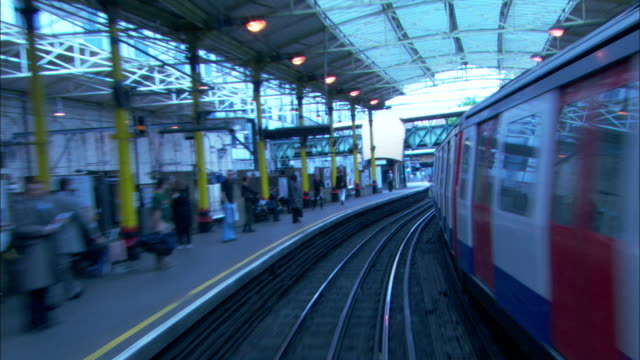 pov push-in - a subway train travels through a tunnel and past the platform where passengers wait. / london, england - bahnreisender stock-videos und b-roll-filmmaterial